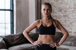 Portrait of strong slim sporty Caucasian young sportswoman wearing black sports bra standing with hands on hips looking at camera in loft studio