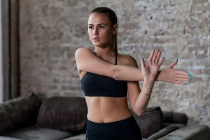 Fit young woman in sportswear doing shoulder and arm stretching exercise before workout indoors in loft apartment