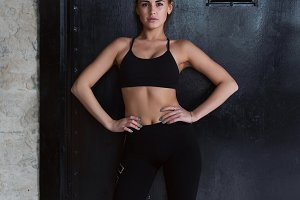 Confident Caucasian fitness model in black sportswear standing hands on hips looking at camera posing against black door