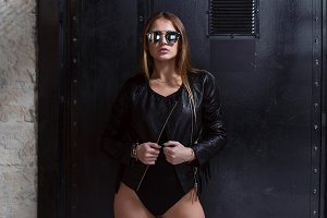 Half-length portrait of sexy young woman wearing sunglasses, black swimsuit and leather jacket posing over dark background