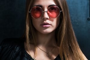 Close up face portrait of beautiful Caucasian young woman with loose hair in fashionable pink round sunglasses looking at camera