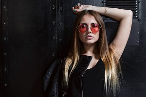 Full face portrait of fashion model in sunglasses with loose long fair hair posing in black surrounding