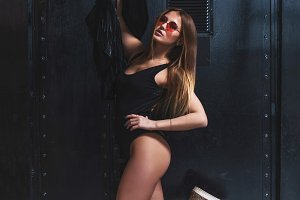 Hot young woman with perfect fit body posing in swimsuit and sunglasses holding a jacket against black background