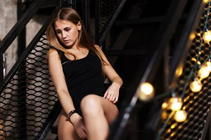 Pretty girl with fair hair wearing black outfit posing sitting on steps of metal fire escape staircase