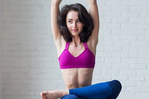 Cute skinny young woman doing toe stand balance posture Padangustasana during yoga session