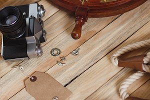 Camera and maritime decorations on the wooden background