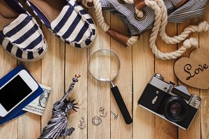 Striped slippers, camera, phone and miniature of the statue of liberty, wooden background