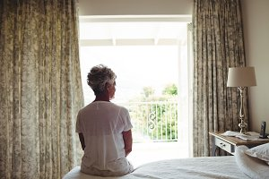 Senior woman sitting on a bed in bedroom