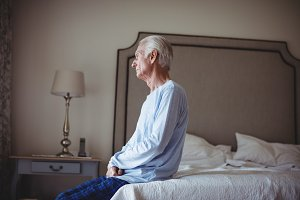 Thoughtful senior man sitting on bed in bedroom