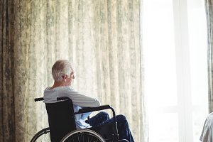 Senior man sitting on wheelchair in bedroom