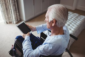Senior man sitting on wheelchair and using digital tablet