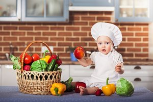 Little girl dressed in white chef hat and apron, sits among vegetables anf holds an apple.