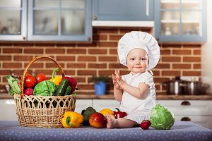 Smiling baby girl dressed in white chef toque and apron