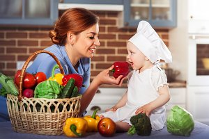 Smiling mother wearing a blue dress feeds charming baby girl cook.