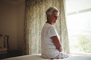 Thoughtful senior woman sitting on a bed in bedroom