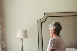 Thoughtful senior woman sitting on bed