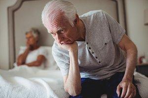 Worried senior man sitting in bed room