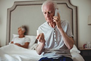 Senior man sitting in bedroom holding medicine and talking on mobile phone