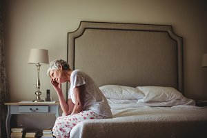 Worried senior woman sitting in bed room