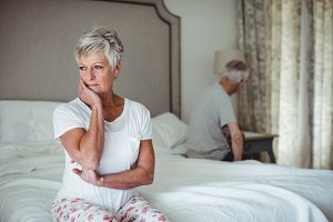 Thoughtful senior woman sitting in bed room