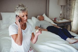 Senior woman sitting in bedroom holding medicine and talking on mobile phone