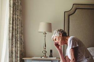 Worried senior woman sitting in bed room