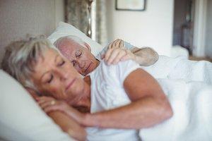 Senior couple sleeping on bed