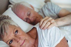 Senior couple lying on bed