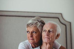 Senior woman embracing senior man on bed