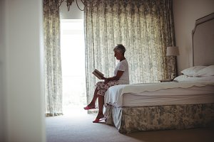 Senior woman sitting on bed and reading book
