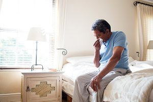 Senior man sneezing nose with handkerchief on bed