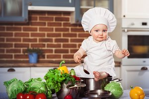 baby sitting astride a stainless pan