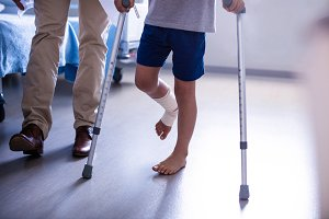 Doctor assisting injured boy to walk with crutches