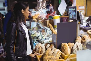 Woman standing at bread counter