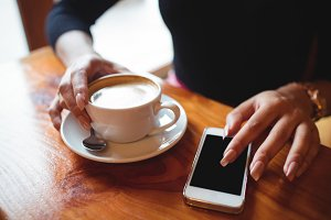 Mid section of woman using mobile phone while having a cup of coffee