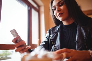 Beautiful woman using mobile phone while having a cup of coffee