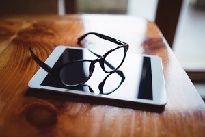 Digital tablet with spectacles on table