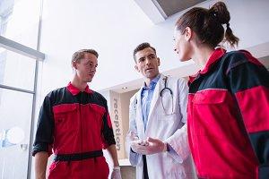 Doctor talking to paramedic in corridor
