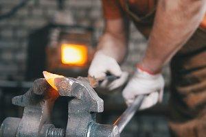 Blacksmith gloves handles a hot metal piece