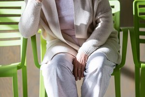 Tensed senior woman sitting on chair in waiting area