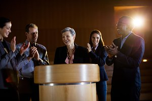 Colleagues applauding speaker after conference presentation