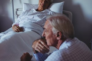Ill woman sleeping on bed while worried man sitting beside her bed