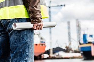 Shipbuilding engineer holding construction documents.