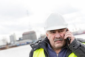Senior engineer builder on the phone at construction site.