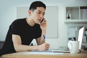 Business executive writing on diary while talking on mobile phone