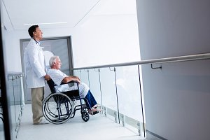 Doctor standing with male senior patient on a wheelchair