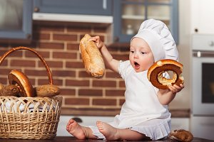 Funny little cook in kitchen with bakery