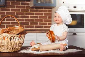 Little smiling baby girl baker in white cook hat and apron