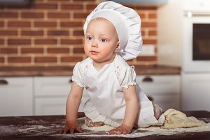 Little baby girl baker in white cook hat and apron