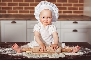 Little smiling baby girl baker in white cook hat and apron kneads a dough